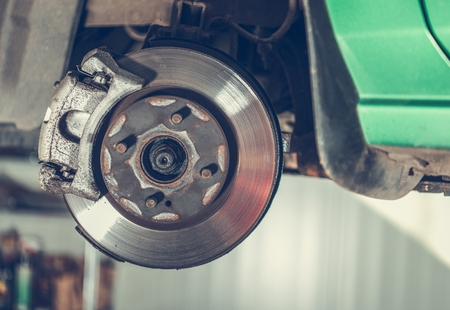 Damaged Car Brake Disc Awaiting Replacement in Auto Service. Automotive Industry.