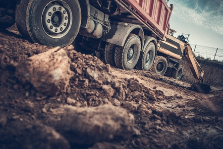 Ground Works Construction Site. Excavator Loading Dump Truck with Soil. Reklamní fotografie