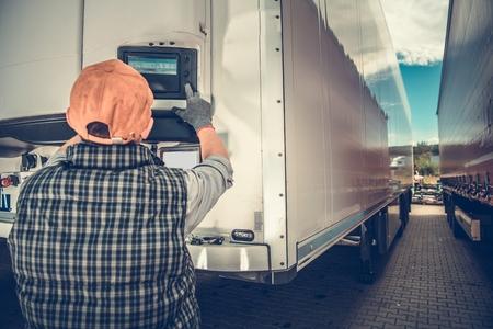 Camionero ajustando la temperatura en el semirremolque frigorífico. Tema de la industria del transporte. Foto de archivo