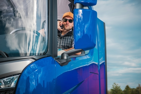 Truck Driver Making Phone Call From Inside His Semi Truck. Transportation Industry. Caucasian Trucker in His 30s.