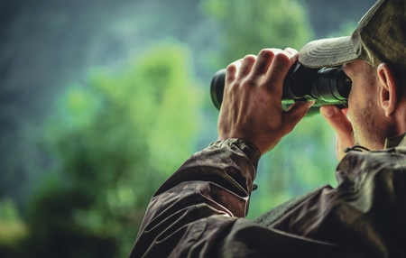 Caucasian Hunter in Camouflage with Binoculars Spotting Wildlife in the Remote Place. Hunting Theme. Reklamní fotografie - 114926182