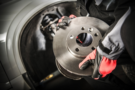 Car Mechanic with Modern Vehicle Brake Disc in Hands. Automotive Theme. Stock Photo