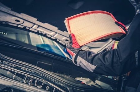 Modern Vehicle Air FIlter Replacement. Car Mechanic with Brand New Filter in Hands.  Automotive Industry Object. Stock Photo