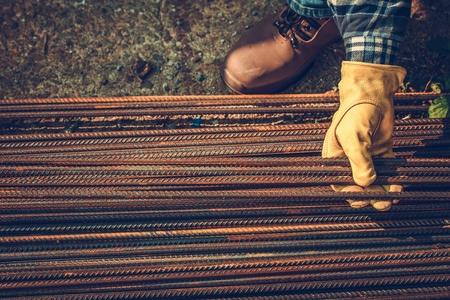 Contractors Hands on the Steel Elements. Steel Reinforcement Bars. Construction Industry.