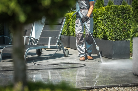 Caucasian Men in His 30s House Patio Water Cleaning Using Pressure Washer. 免版税图像