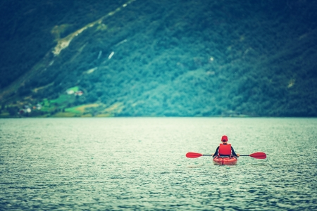 Active Day in a Kayak. Caucasian Kayaker on the Glacial Lake.