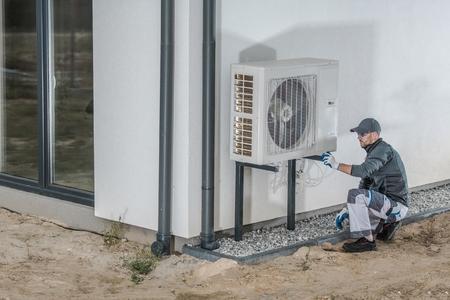 Projekt zur Installation von Wärmepumpen. Kaukasischer Heizungs- und Kühlungstechniker, der ein neues Gerät installiert.
