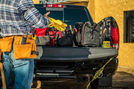 Industria Empresarial de la Construcción. Trabajador contratista caucásico preparándose para el trabajo usando guantes de seguridad frente a su camioneta llena de herramientas necesarias. Foto de archivo