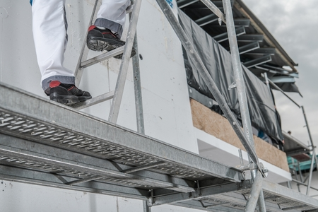 Worker in a Scaffolding. Construction Safety Elements.