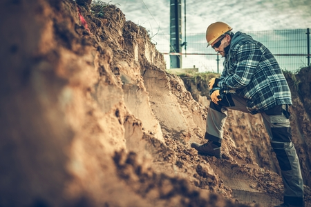 Caucasian Construction Worker Checking on a Soil Within Building Area.