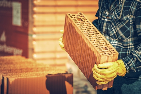 Ceramic Perforated Building Block in Construction Worker Hands. Industrial Theme. Imagens