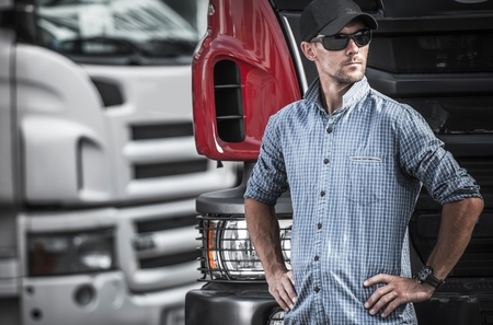 Trucker and the Transport Industry. Caucasian Men in His 30s In Front of His Semi Truck. Stock Photo