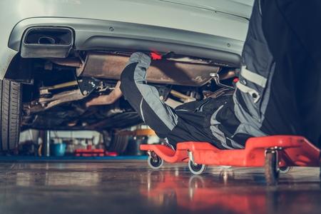 Mecánico de vehículos de raza caucásica en sus 30 años de reparación de vehículos tendido debajo del vehículo en la enredadera. Industria automotriz. Foto de archivo