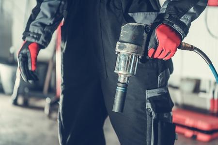 Car Mechanic with Air Impact Wrench Pneumatic Gun. Automotive Industry. Banco de Imagens