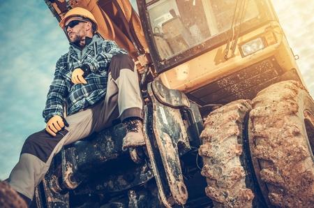 Caucasian Excavator Operator Sitting on His Excavator. Heavy Duty Ground Working Machinery. Construction Industry.
