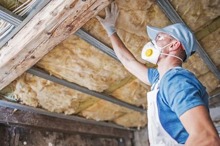 Isolamento del vecchio tetto. Operaio edile caucasico nei suoi 30 anni che ispeziona il tetto invecchiato e l'isolante in lana minerale.