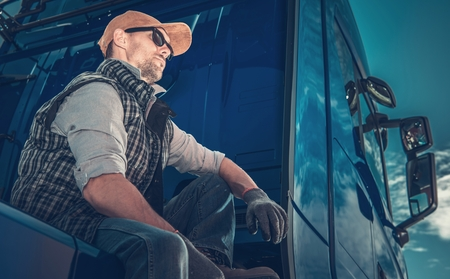 Caucasian Truck Driver Wearing Sunglasses Taking Short Break on the Truck Stop. Stock Photo