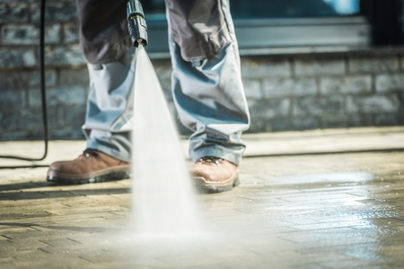 Men Using Pressure Washer For Driveway Cleaning. Фото со стока