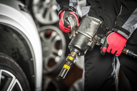 Auto Service Worker with Heavy Duty Pneumatic Gun Preparing For Seasonal Tire Changes.