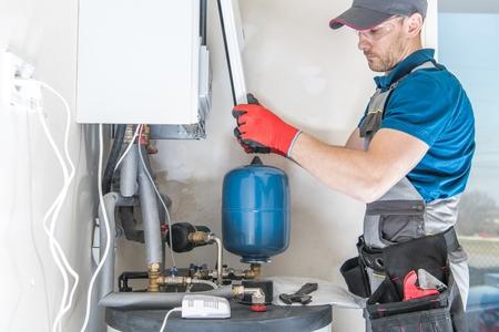 Instalación de calentador de gas central por un instalador profesional de sistemas de calefacción caucásico. Foto de archivo