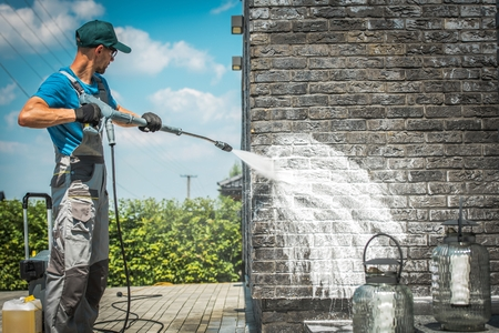 Brick House Wall Pressure Washing with Special Cleaning Detergent. Caucasian Men in His 30s. Taking Care of the Building Elevation. Stock Photo - 117305966