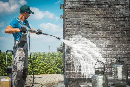 Mycie ciśnieniowe ścian Brick House ze specjalnym detergentem czyszczącym. Kaukascy mężczyźni po trzydziestce. Dbanie o elewację budynku.