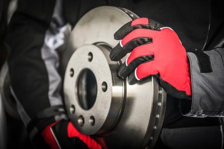 Modern Ventilated Car Brake Disc in Mechanics Hands. Automotive Theme.