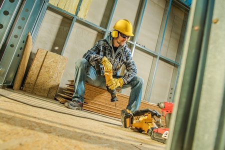 Construction Worker with Cordless Reciprocating Saw in Hands Taking Short Brake While Seats on the Pile of Plywood Boards. Construction Industry Theme.