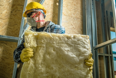 Caucasian Construction Worker Wearing Safety Mask Moving Pieces of Mineral Wool Insulation.