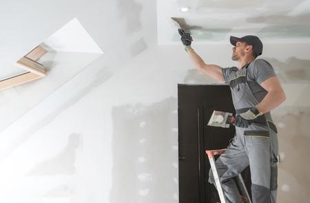 Fertigstellung und Ausbesserung von Trockenbauwänden durch einen kaukasischen Remodeler in seinen 30ern. Baugewerbe. Standard-Bild