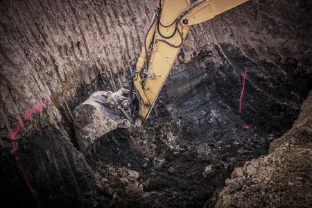 Construction Excavation Site. Excavator Digging Inside Large Ground Hole. 版權商用圖片