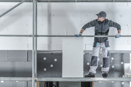 Modern House Insulation. Construction Worker Installing Molded Graphite Polystyrene. Stockfoto