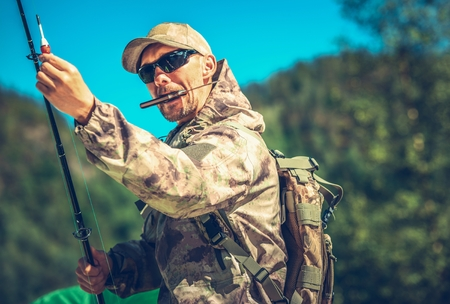 Caucasian Fisherman in His 30s with Knife in Mouth Preparing For a Fly Fishing.