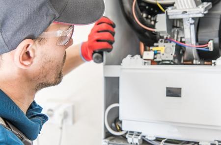 Reparación de calentador central de gas natural por un técnico profesional de calefacción caucásico.