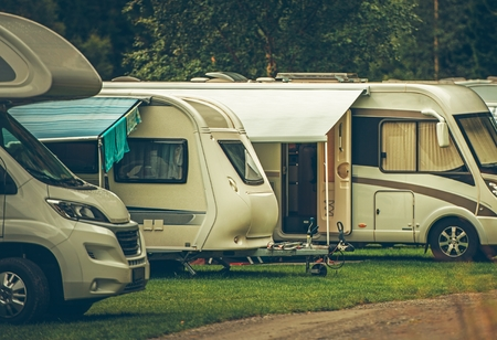 RV Park Camping. Modern Recreational Vehicles on the Campsite. Motorhomes and Travel Trailers.