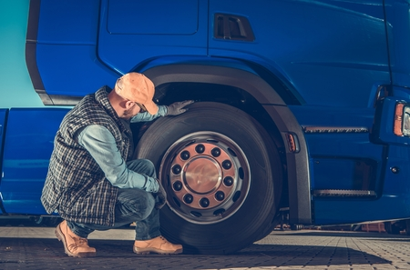 Caucasian Driver Checking Semi Truck Wheels Looking For Potential Issues. Transportation Industry Safety. Stockfoto