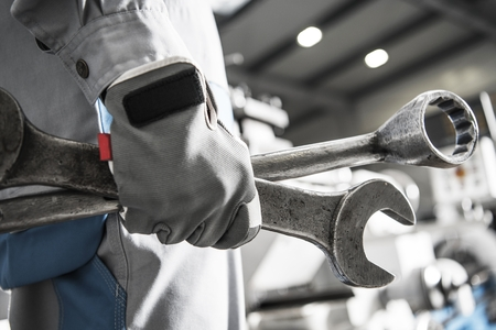 Large Machinery Fixing. Mechanic with Heavy Duty Wrenches in Hand. Closeup Photo. Reklamní fotografie