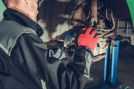 Automotive Industry. Car Brakes Maintenance Performed by Caucasian Auto Service Mechanic. 版權商用圖片