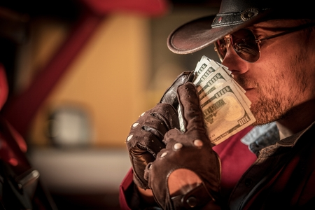 Caucasian Cowboy in Sunglasses and Western Style Hat Sniffing His Money.
