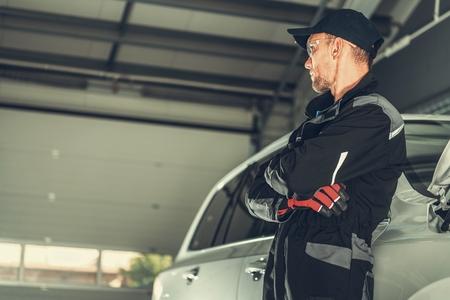 Car Mechanic Profession. Caucasian Men in His 30s Inside His Vehicle Repair Shop