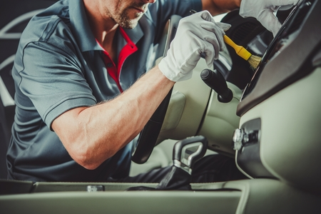Caucasian Automotive Industry Worker Detailing Car Interior. Vehicle Cleaning Maintenance.