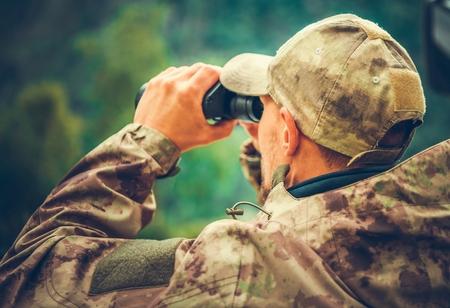 Caucasian Hunter Spotting Game Using Binoculars. Hunting Season.
