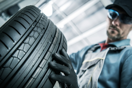 Automotive Worker Replacing Car Tires with New One. Reklamní fotografie