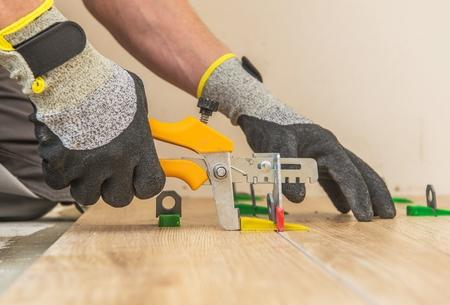 Ceramic Tiles Leveling System. Worker Installing Leveling Separators Between Floor Tiles.