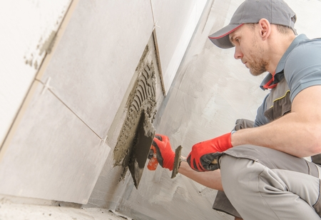 Bathroom Ceramic Tiles Installer. Caucasian Construction Worker in His 30s.