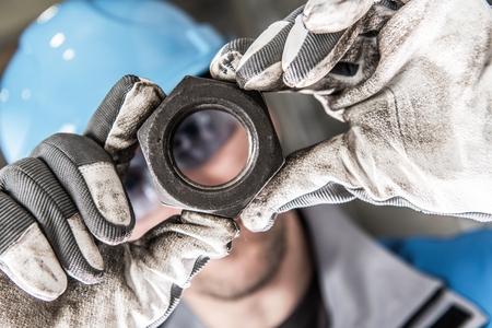 Metallic Hexagon Nut in Worker Hands Closeup Photo. Metalworking Industry.