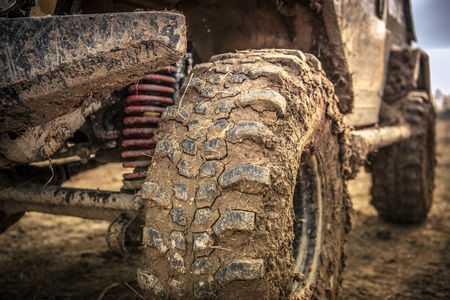Off Roader Tire Closeup. SUV Wheel Covered by Clay and Mud. Motorsport Theme.