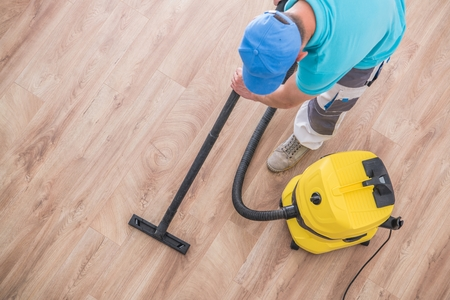 Caucasian Men Vacuuming Apartment New Hardwood Floor. Home Cleaning Time.