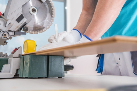 Contractor Worker Measuring Piece of Hardwood Before Cut Using Circular Saw. Construction Industry. Reklamní fotografie