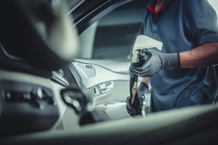 Professional Car Cleaning Service. Caucasian Worker with Wet Dry Vacuum in Hands Preparing For Interior Fabrics Washing. Reklamní fotografie